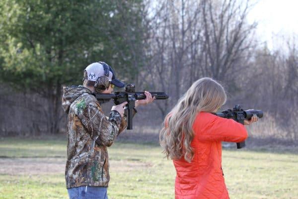 Man and woman shoot guns toward targets while wearing eye and ear protection